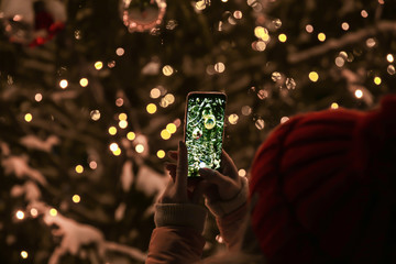 Woman taking picture of beautifully decorated Christmas tree outdoors