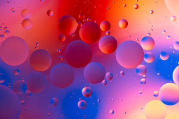 orange gradient oily drops circling in water with colorful background, close-up
