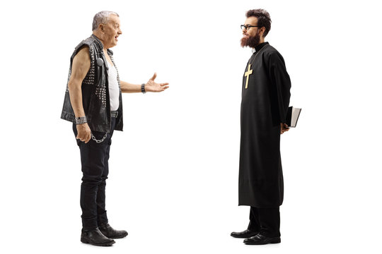 Mature male punker in a leather vest talking to a priest