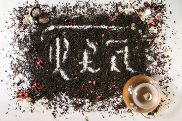 Calligraphic inscription gothic letters tea over dry black ceylon and green tea scattered on white marble with rose buds, stainer, glass teapot. Tea drinking concept background. Top view