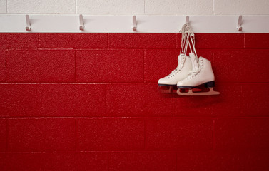 Figure skates hanging over red wall in locker room with copy