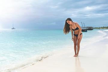 Attractive slim brown-haired woman in a bikini on a white sandy paradise beach Kendwa of Indian Ocean of Zanzibar island
