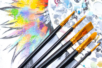 professional art brushes with a palette for color matching on a bright and multicolored background