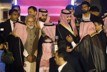 India's Prime Minister Narendra Modi looks on as Saudi Arabia's Crown Prince Mohammed bin Salman meets the officials upon his arrival at an airport in New Delhi