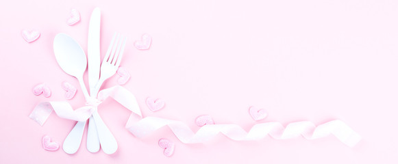 Festive table setting for Valentines Day with fork, knife and hearts  on pink pastel background.Romantic dinner. Space for text. Top view.Banner