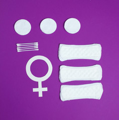 Products for feminine hygiene, self-care and health, female gender symbol on a purple background. Ear sticks, pads. Top view
