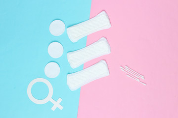 Products for feminine hygiene, self-care and health, female gender symbol on pastel background. Ear sticks, pads. Top view
