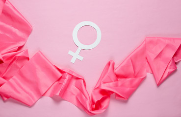Female gender symbol, silk ribbon on pastel pink background. Minimalism. Top view