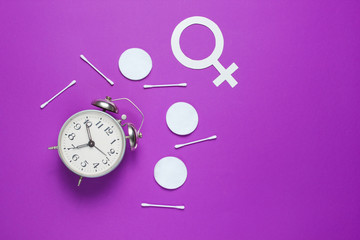 Self care time. Products for hygiene, female gender symbol, retro alarm clock on purple  background. Top view. Flat lay