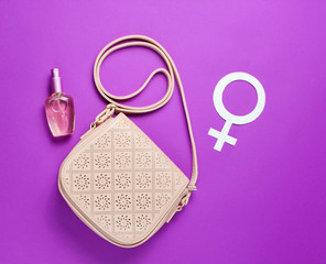 Women's fashion bag, perfume bottle, gender feminism symbol on  purple background. Top view. Minimalism