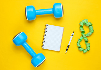 Fitness concept, workout plan. Plastic blue dumbbells, notepad, ruler on a yellow background. The idea of ​​losing weight. Top view. Flat lay
