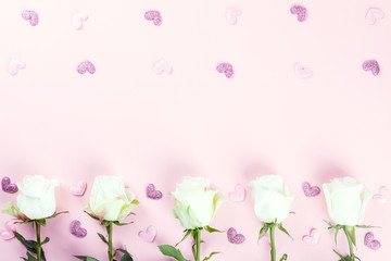 Valentines Day composition. White rose flowers on pastel pink background. Confetti heart shaped. Mothes day, Womens Day Holiday concept. Flat lay, top view, copy space.
