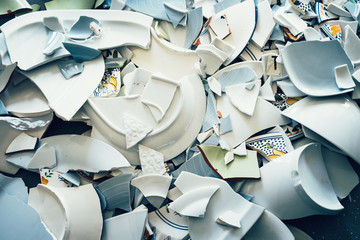Shards of broken crockery ceramic plates cups and porcelain on the floor