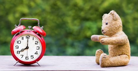 Daylight savings time concept - web banner of a red retro alarm clock and a toy bear