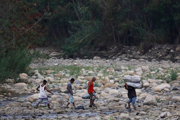 People, working as 'Maleteros', carry merchandise as they crosse the Tachira river on the outskirts of Cucuta