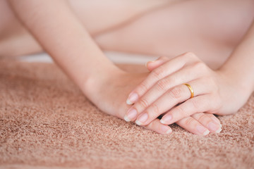 The woman's hand is placed on the towel, the concept of health care of the fingernail.