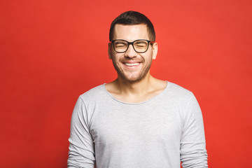 Charming handsome. Handsome cheerful young man in casual wear smiling while standing isolated on red background.