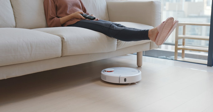 Woman lift up the feet for letting vacuum pass though