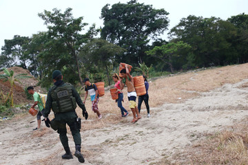 A Colombian police officer checks people as he patrols the trails during an anti-smuggling operation on the outskirts of Cucuta