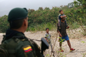 A Colombian police officer patrols the trails as a man and his sons walk near the Tachira river during an anti-smuggling operation on the outskirts of Cucuta