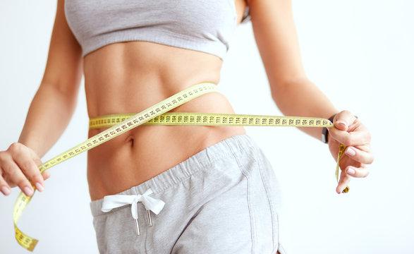 Crop slender woman measuring waist line