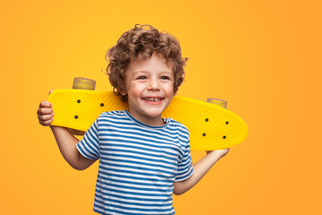 Charming boy with bright longboard