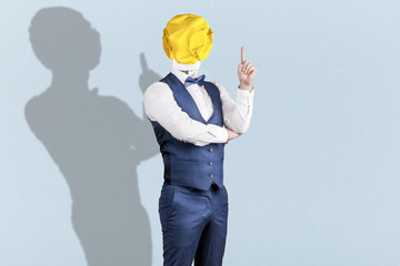 Wall Mural - a man on blue background in a suit with a light bulb of crumpled yellow paper instead of a head with a raised finger, the concept of the idea