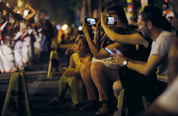 A girl watches as others take pictures of the dancers during the annual Nawam Maha Perahera of Gangaramaya Buddhist temple in Colombo