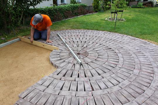 Ein Mann verlegt Steine für eine Terrasse