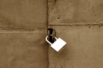 Old padlock on metal gate in brown color.