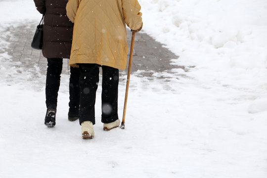 Woman walking with a cane during snowfall. Concept of limping, old age, winter weather, elderly or blind person