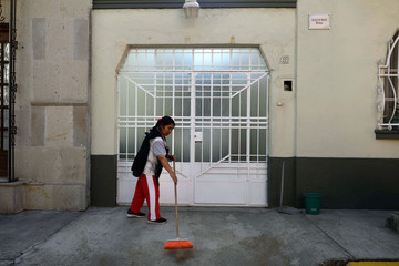 """Margarita, a domestic employee in the house where """"Roma"""" movie directed by Alfonso Cuaron was filmed, sweeps the sidewalk at Tepeji street in Roma neighborhood, in Mexico City"""