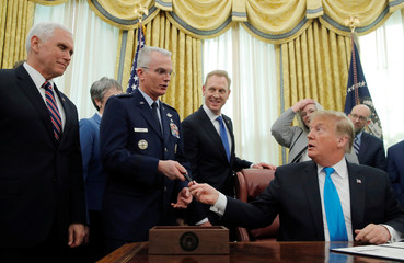 U.S. President Donald Trump hands the pen to Vice Chairman of the Joint Chiefs of Staff U.S. Air Force General Paul Selva in the Oval Office at the White House in Washington