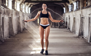 Young woman in sportswear doing exercise with skipping rope in the abandoned industrial building