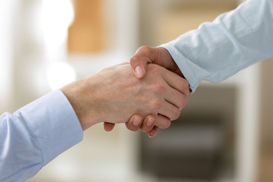 Close up male female hands shaking hands