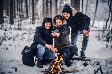 Cheerful friends of travelers do Sefli sitting by the fire in the midst of a snowy forest