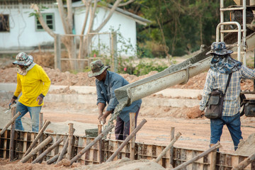 NAKHON PHANOM, THAILAND - DEC 24, 2018 : Concrete mixer truck. Workers are pouring concrete in site building construction