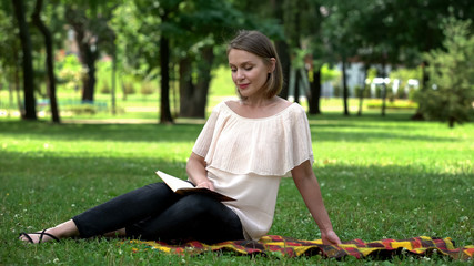 Calm pretty woman reading book about self-development in park, leisure time