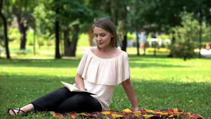 Pretty lady reading romantic novel, sitting on plaid in park, book lover