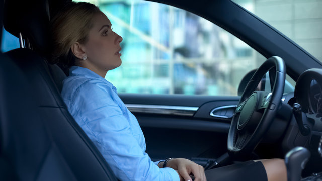Upset woman tired after working day, sitting in car, thinking over problems