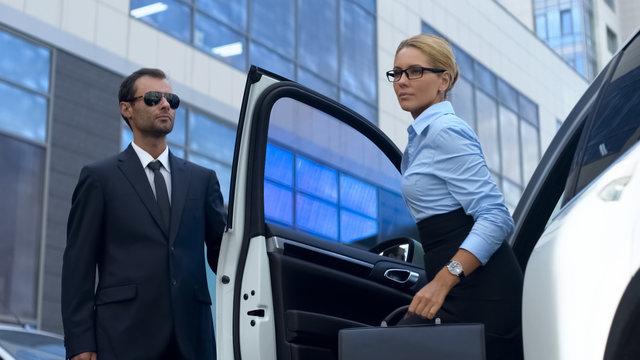 Bodyguard in suit opening car door to female boss, luxury service, success