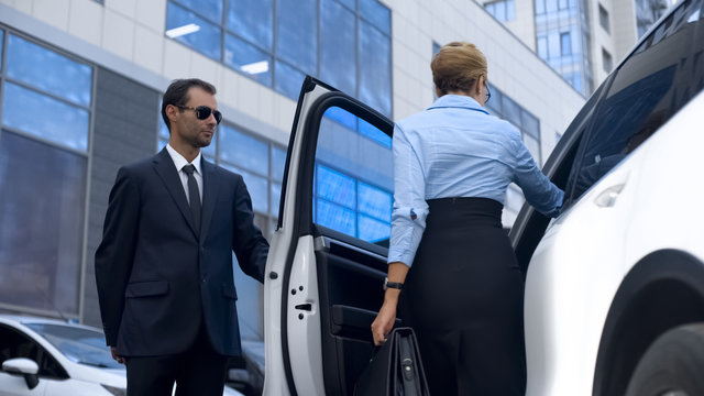 Personal assistant of female politician opening car door to his boss, service