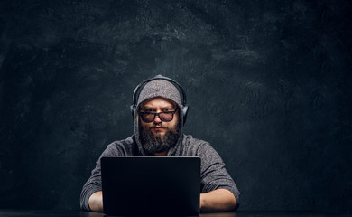 A hacker sits behind a laptop in a dark room and stares intently at the camera