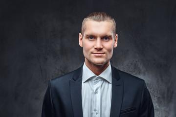 A confident businessman in black suit wearing elegant black suit. Studio shot on a dark textured wall