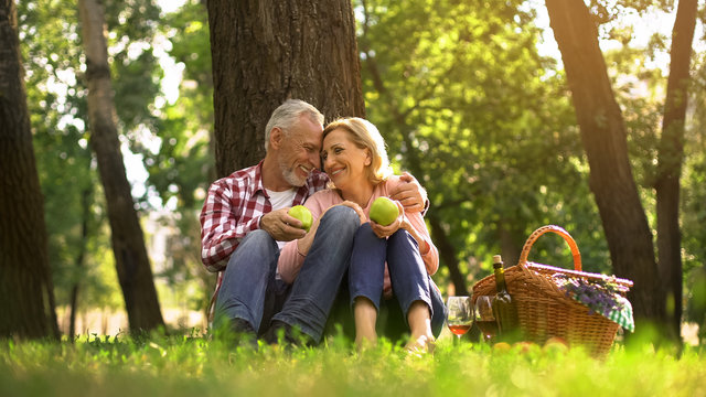 Loving old couple hugging in park and eating green apples, picnic family weekend