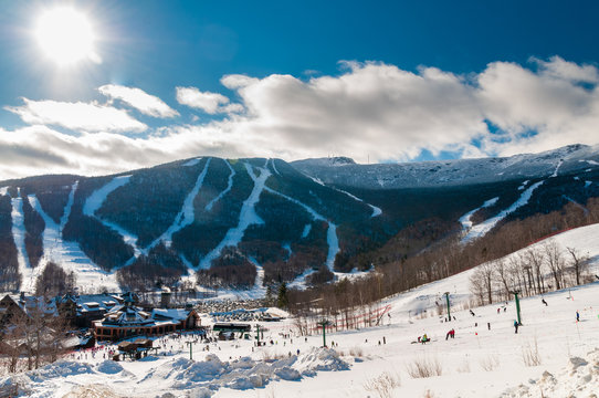 Spruce Peak Lodge in the winter with Mt. Mansfield in the background, Stowe, Vermont, USA