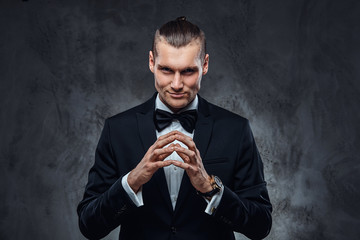 A confident man wearing a black classical suit and bow tie, looking at a camera. Studio shot on a dark textured wall