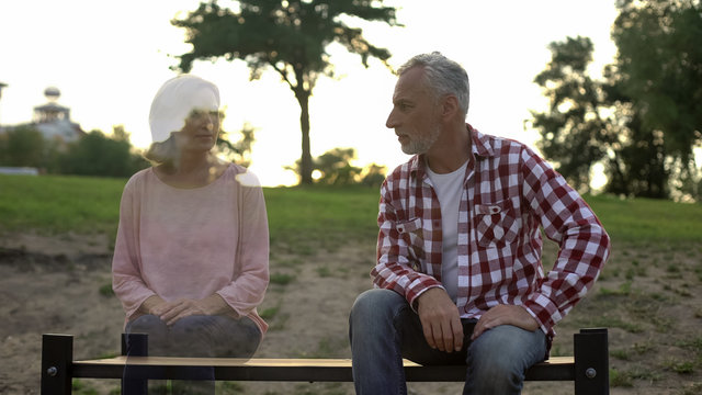 Lonely pensioner sitting on bench, wife appearing beside, loss sorrow, memories
