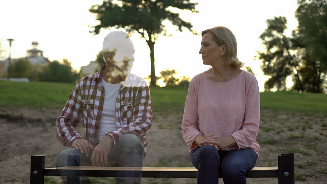 Depressed old woman sitting on bench, husband appearing beside, loss, memories
