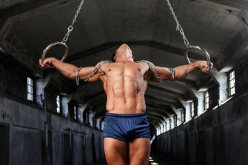 Graceful muscular sportsman workouts in the air with gymnastic rings, training in an abandoned industrial building